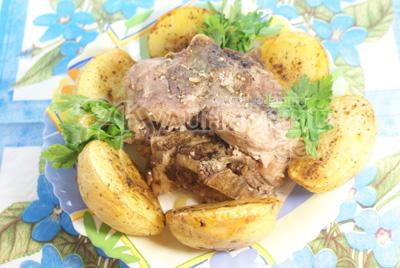 Викладаємо в середину страви м'ясо, а по краях половинки картоплі, прикрашаємо зеленню. - Запечена свинина на кісточці з картоплею .